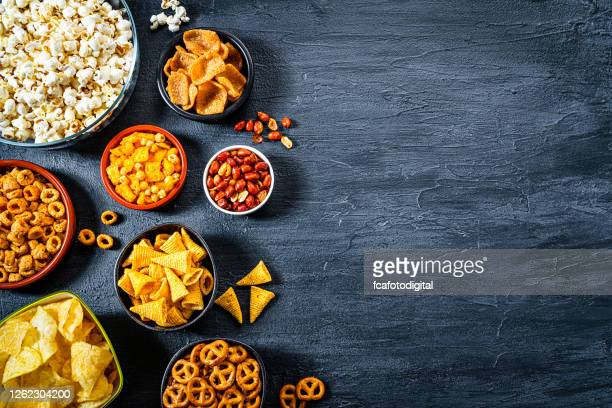 salty snacks assortment shot from above on dark slate table. copy space - cracker snack stock pictures, royalty-free photos & images