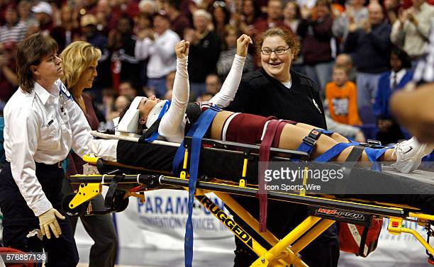 A Salukis cheerleader is taken off the floor on a stretcher after falling from the top of a pyramid during a timeout during the Southern Illinois...