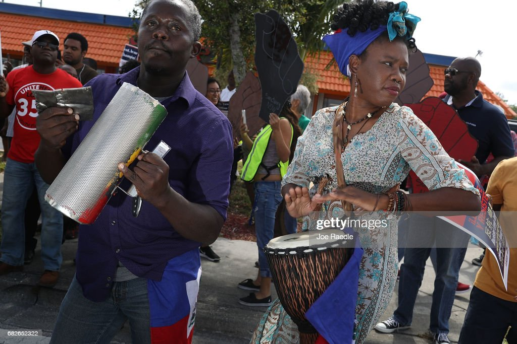 Salusa Bosquin (L) and Cherdeline Pierre Louis join others as they protest the possibility that the Trump administration may overturn the Temporary Protected Status for Haitians in front of the U.S. Citizenship and Immigration Services office on May 13, 2017 in Miami, Florida. 50,000 Haitians have been eligible for TPS and now the Trump administration has until May 23 to make a decision on extending TPS for Haitians or allowing it to expire on July 22 which would mean possibly deportation for the current TPS holders.