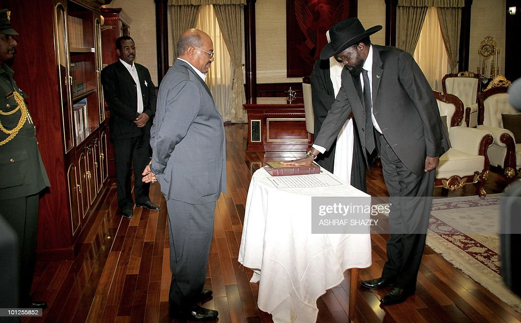 Salva Kiir (R), who heads Sudan's former rebel SPLM, swears on the bible in front of veteran Sudanese President Omar al-Beshir during a swearing in ceremony for the vice-presidents at the persidential palace in Khartoum on May 29, 2010, following last month's elections in which Beshir, who faces international war crimes charges, was reelected for a new five-year term.