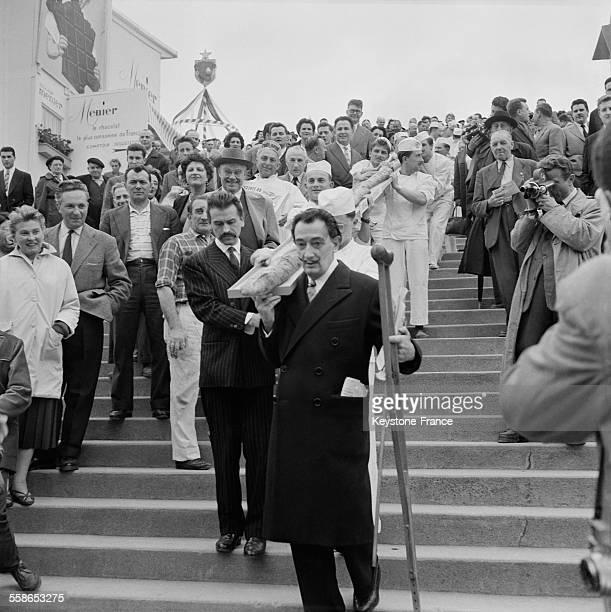 Salvador Dali accompagné par plusieurs boulangers transporte une baguette de pain de 12 m de long réalisée pour une conférence au théâtre de l'Etoile...