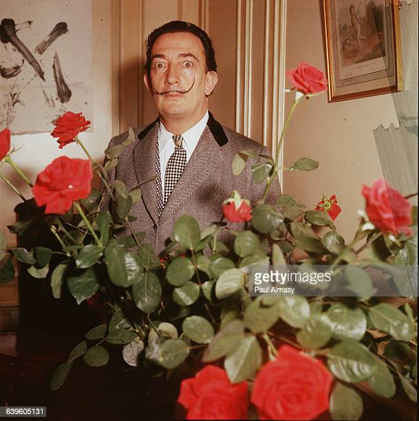 Salvador Dali posing behind a bunch of red roses. France, ca. 1960s.