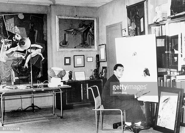 Salvador Dali Spanish Surrealist painter is shown seated in his studio by a workinprogress looking at the photographer