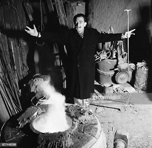Salvador Dali works on the bronze cover for the book The Apocalypse of St John Seven painters and writers including Jean Cocteau and Fujita will...