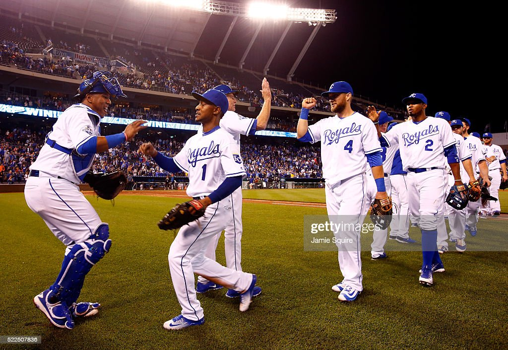 Salvador Perez #13 and Jarrod Dyson #1 of the Kansas City Royals high five as the rest of the team celebrates on the field after the Royals defeated the Detroit Tigers 8-6 to win the game at Kauffman Stadium on April 19, 2016 in Kansas City, Missouri.