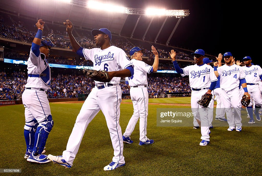 Salvador Perez #13 and Lorenzo Cain #6 of the Kansas City Royals high five as the rest of the team celebrates on the field after the Royals defeated the Detroit Tigers 8-6 to win the game at Kauffman Stadium on April 19, 2016 in Kansas City, Missouri.