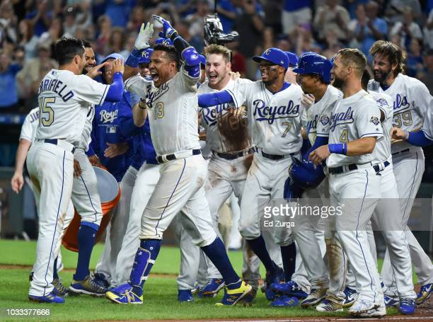 Salvador Perez celebrates with Whit Merrifield and members of the Kansas City Royals as he celebrates his walk-off grand slam against the Minnesota...
