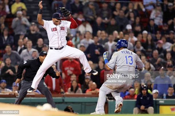 Salvador Perez of the Kansas City Royals beats the tag from Rafael Devers of the Boston Red Sox during the eighth inning at Fenway Park on May 1 2018...
