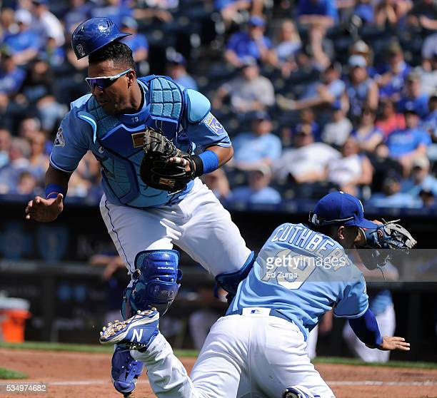 Salvador Perez of the Kansas City Royals catches a foul ball hit by Adam Eaton of the Chicago White Sox as he collides into Cheslor Cuthbert in the...