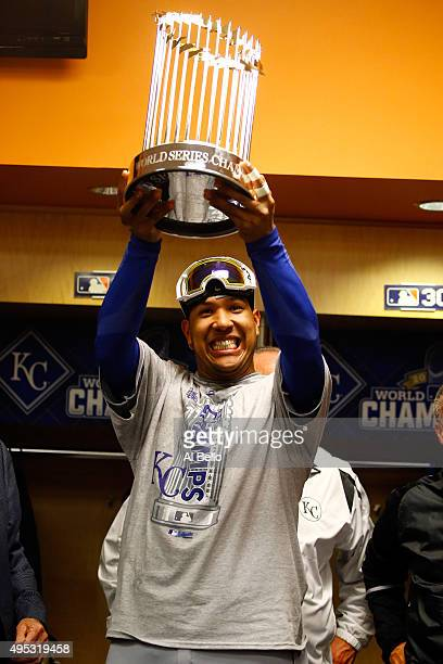 Salvador Perez of the Kansas City Royals celebrates in the clubhouse with the Commissioner's Trophy after defeating the New York Mets to win Game...
