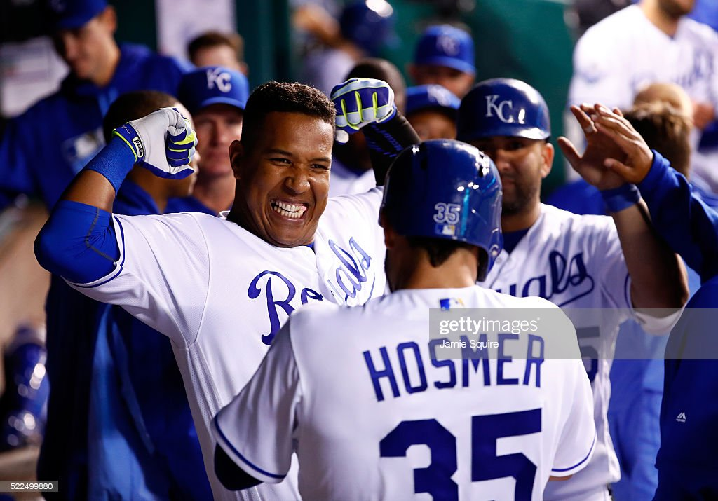 Salvador Perez #13 of the Kansas City Royals celebrates with Eric Hosmer #35 and Kendrys Morales #25 in the dugout after hitting a 3-run home run during the 5th inning of the game against the Detroit Tigers at Kauffman Stadium on April 19, 2016 in Kansas City, Missouri.