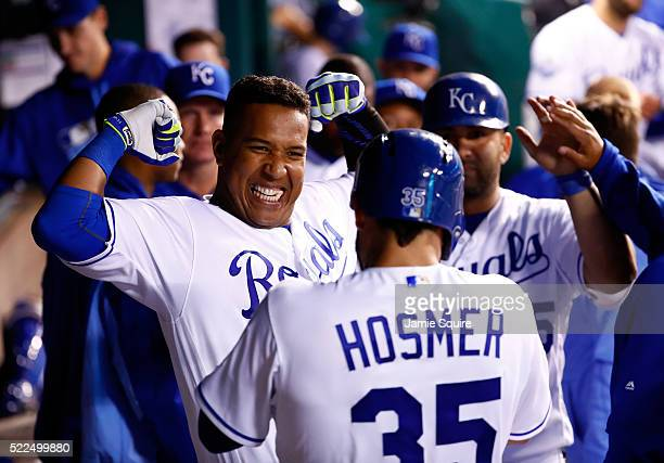 Salvador Perez of the Kansas City Royals celebrates with Eric Hosmer and Kendrys Morales in the dugout after hitting a 3run home run during the 5th...