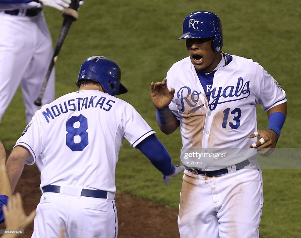 Salvador Perez #13 of the Kansas City Royals celebrates with Mike Moustakas #8 after scoring on a Lorenzo Cain triple in the sixth inning against the Cleveland Indians at Kauffman Stadium on September 16, 2013 in Kansas City, Missouri.
