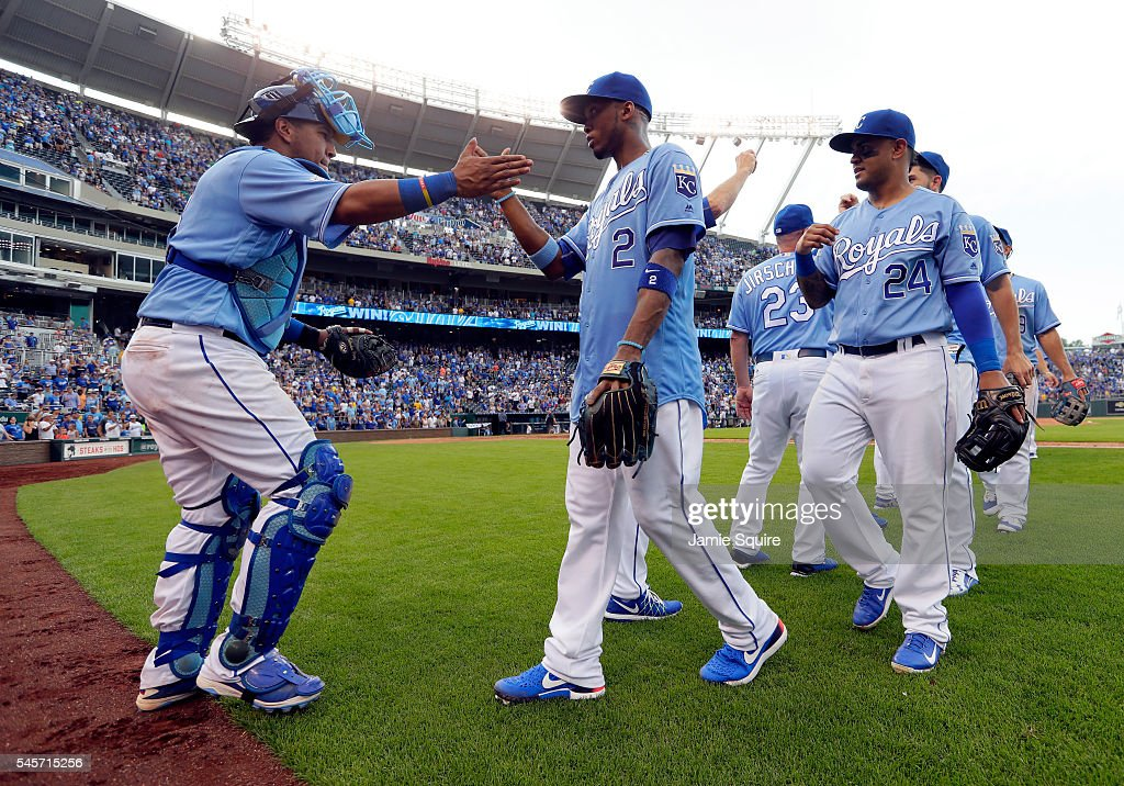 Salvador Perez #13 of the Kansas City Royals congratulates Alcides Escobar #2 and teammaotes after the Royals defeated the Seattle Mariners 5-3 to win the game at Kauffman Stadium on July 9, 2016 in Kansas City, Missouri.