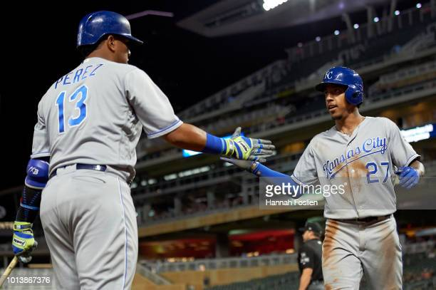 Salvador Perez of the Kansas City Royals congratulates teammate Adalberto Mondesi on scoring against the Minnesota Twins during the game on August 3...