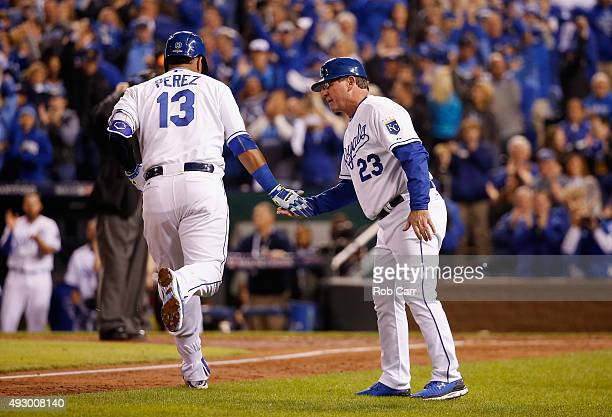 Salvador Perez of the Kansas City Royals is congratulated by Mike Jirschele of the Kansas City Royals after hitting a solo home run in the fourth...
