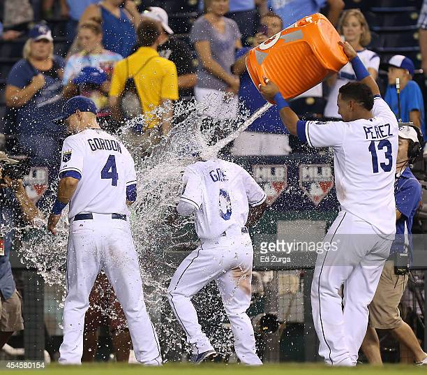 Salvador Perez of the Kansas City Royals pours water on Alex Gordon and Terrance Gore after a 41 win over the Texas Rangers at Kauffman Stadium on...