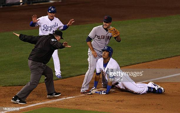 Salvador Perez of the Kansas City Royals reacts as third base umpire Bill Welke calls him safe on a triple as Lonnie Chisenhall of the Cleveland...