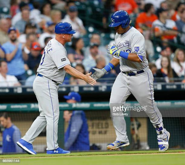 Salvador Perez of the Kansas City Royals receives congratulations from third base coach Mike Jirschele after hitting a home run in the second inning...
