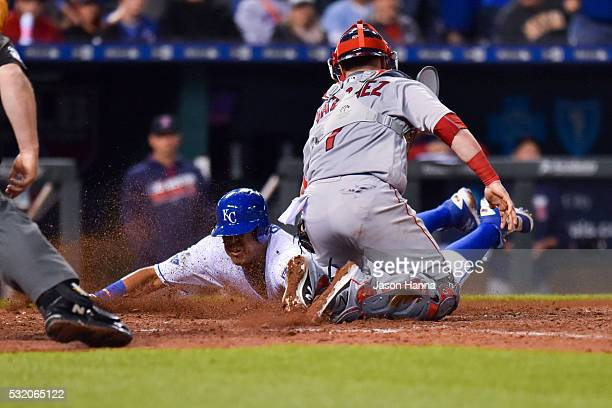 Salvador Perez of the Kansas City Royals slides home to score a run after a wild throw to first base from Koji Uehara of the Boston Red Sox in the...