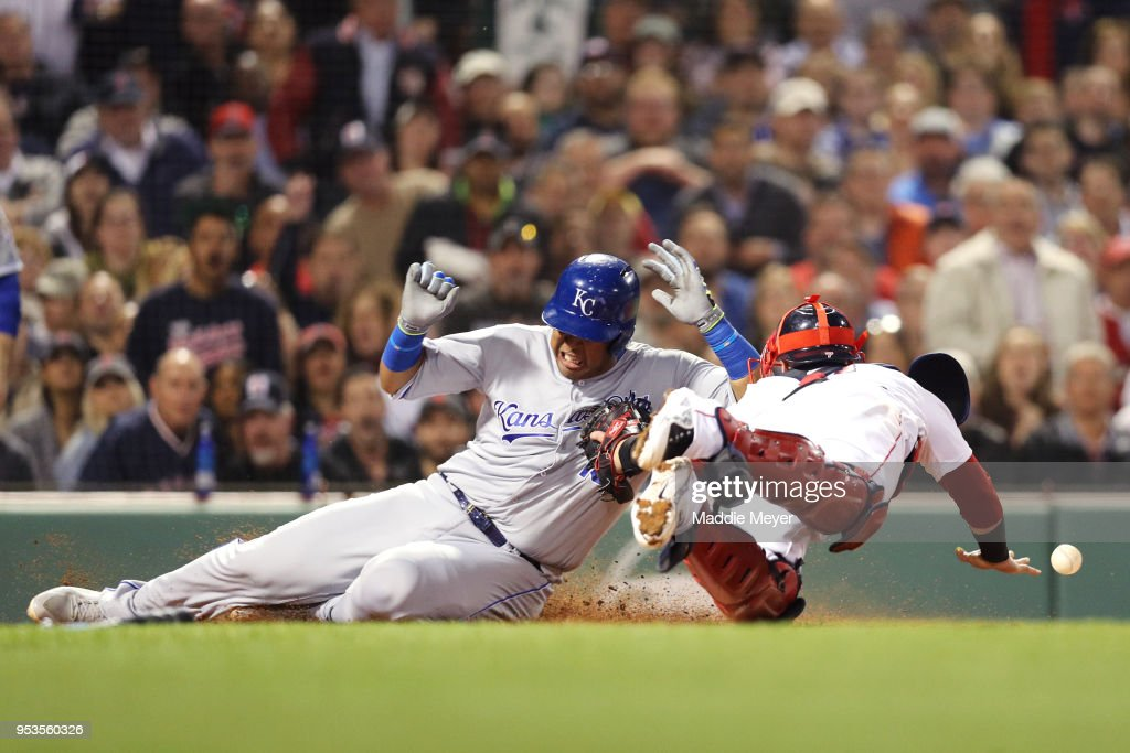 Salvador Perez #13 of the Kansas City Royals slides into home plate scoring a run past Christian Vazquez #7 of the Boston Red Sox during the fourth inning at Fenway Park on May 1, 2018 in Boston, Massachusetts.