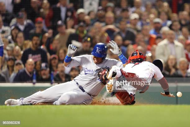 Salvador Perez of the Kansas City Royals slides into home plate scoring a run past Christian Vazquez of the Boston Red Sox during the fourth inning...