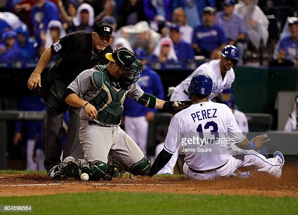 Salvador Perez of the Kansas City Royals slides safely into home to score as catcher Stephen Vogt of the Oakland Athletics drops the ball during the...