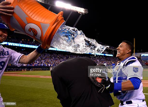 Salvador Perez of the Kansas City Royals takes cover behind Fox Sports Kansas City's Joel Goldberg as he avoids being hit by a water douse from...