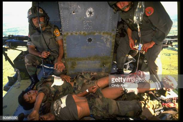 Salvadoran Air Force helicopter personnel aiding ground troops wounded in heavy fighting w guerrillas on rescue mission evacuating them