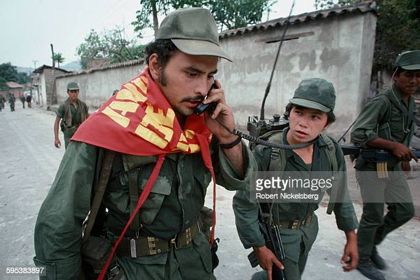 Salvadoran army officer speaks on a radio set after the soldiers entered into the village occupied earlier by the guerrillas from the Frente...