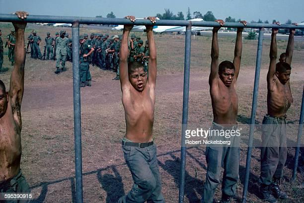 Salvadoran Army recruits hang from a crossbar during a parachute training exercise at the Ilopongo airport San Salvador El Salvador January 1 1982 At...