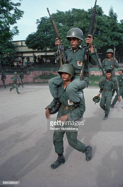 Salvadoran Army recruits train, one carrying another on his shoulders, at an unidentified army base, El Salvador, July 1, 1982. At the time, the...