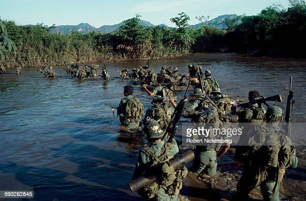 Salvadoran army soldiers from the Atlacatl Rapid Reaction Battalion cross a river during a military operation against guerrillas from the People's...