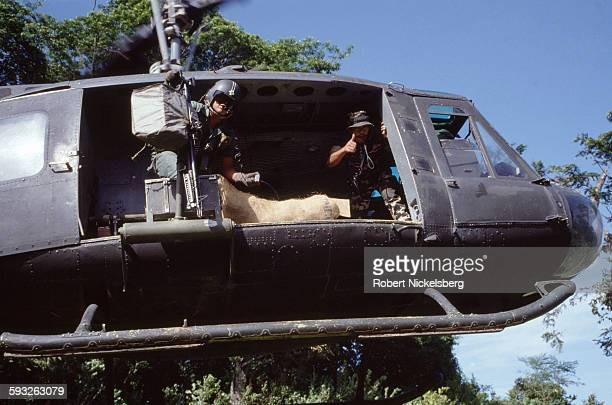 Salvadoran army soldiers move a helicopter into position during a food and ammunition resupply drop for the Atlacatl Rapid Reaction Battalion in San...