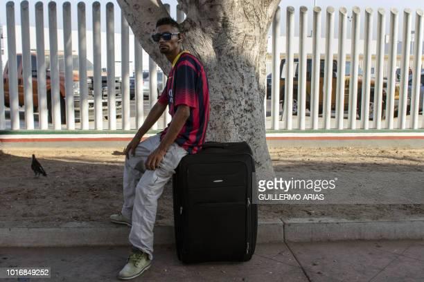 Salvadoran asylum seeker Jaime Rene Delgado sits on top of his luggage at El Chaparral port of entry in Tijuana Baja California state Mexico on...