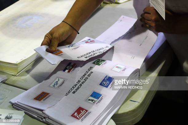 Salvadoran electoral officials destroy unused electoral material at a polling station during legislative and municipal elections in San Salvador on...