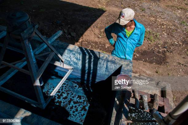 Salvadoran farm worker watches the indigo process while water solution is slowly siphoning out from a concrete tank at the semiindustrial manufacture...