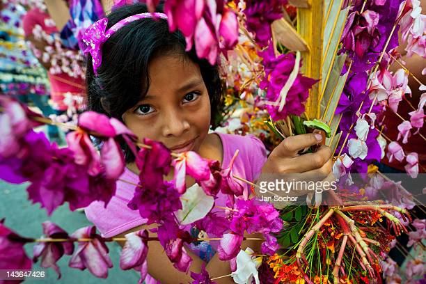 Salvadoran girl carries a palm branch with colorful flower blooms during the procession of the Flower Palm Festival in Panchimalco El Salvador 8 May...