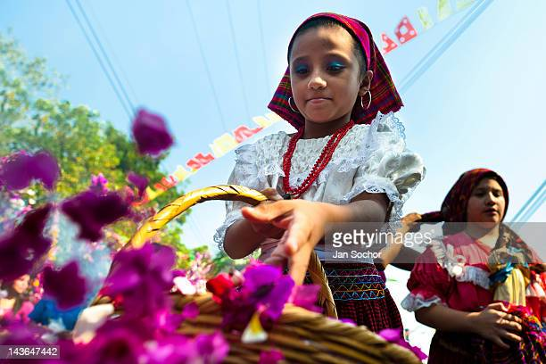 Salvadoran girl throws colorful flower blooms during the procession of the Flower Palm Festival in Panchimalco El Salvador 8 May 2011 On the first...