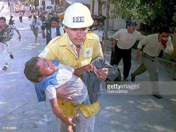 Salvadoran Green Cross rescue worker carries a child to safety 29 March after the child was overwhelmed by teargas during clashes between police and...