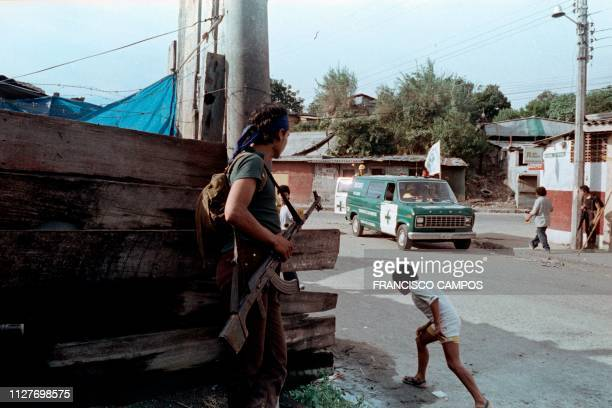 Salvadoran guerilla watches the arrival of an ambulance in the Mejicanos neighborhood of San Salvador on November 12, 1989. - The guerillas launched...