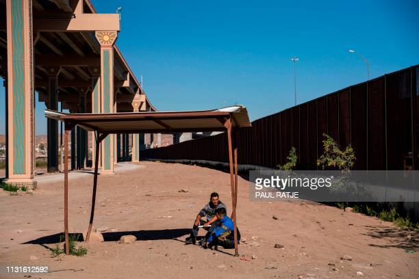 Salvadoran migrants sit near the US border fence after crossing the Rio Grande to claim asylum in El Paso Texas on March 19 2019 Speaking of an...