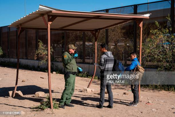 Salvadoran migrants speak with a member of the US border patrol by the border fence after crossing the Rio Grande to claim asylum in El Paso Texas on...