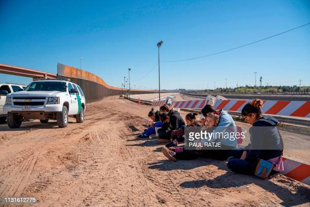 Salvadoran migrants wait for a transport to arrive after turning themselves into US Border Patrol by border fence under construction in El Paso,...