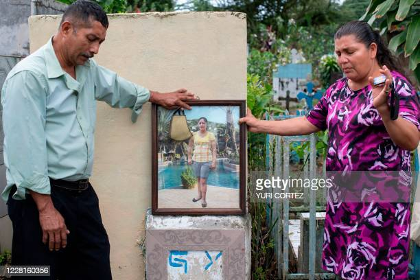 Salvadoran Mirna del Carmen Solorzano and her husband Miguel Angel Medrano visit the grave of their daughter Glenda, at the municipal cemetery in...