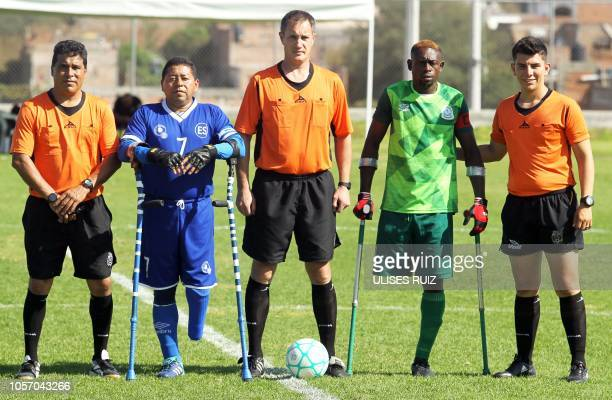 Salvadoran player Jose Nava and Nigerian footballer Michael Chimobi pose for pictures along with referees after their 2018 Amputee Football World Cup...