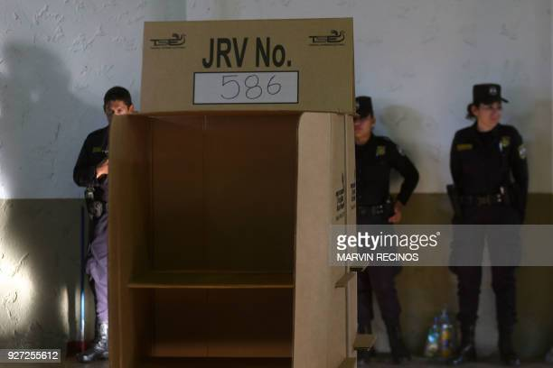 Salvadoran police officers stand guard at a polling station during legislative and municipal elections in San Salvador on March 4 2018 Legislative...
