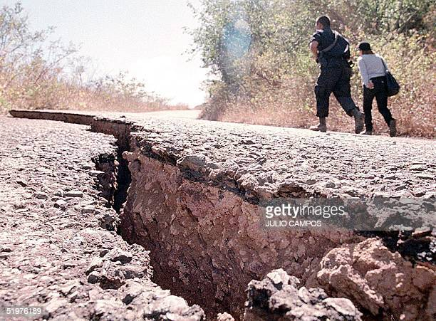 Salvadoran police walk down a paved street near Santa Ana El Salvador ripped open by a massive earthquake 13 January 2001 At least 109 people were...