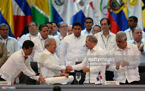 Salvadoran President Salvador Sanchez Ceren receives the pro tempore presidency from his Dominican Republic counterpart Danilo Medina during the...