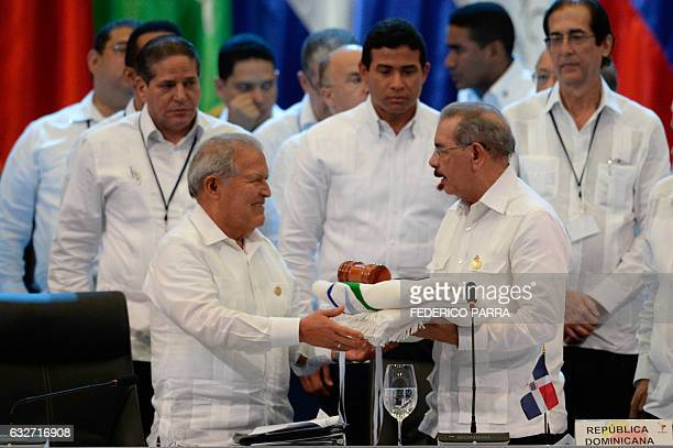 Salvadoran President Salvador Sanchez Ceren receives the pro tempore presidency from his Dominican Republic counterpart Danilo Medina during the...